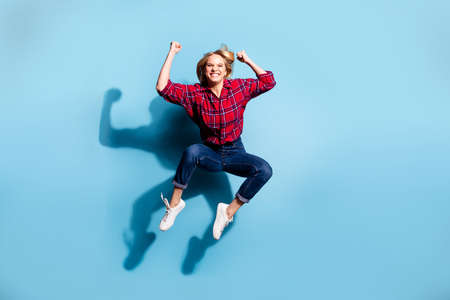 Full length body size view portrait of nice charming attractive cheerful cheery teen girl wearing checked shirt flying celebrate isolated on teal turquoise bright vivid shine background