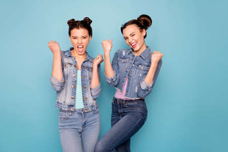 Portrait of funky cheerful positive cute students fellows winning reaching goals satisfaction raising fists yelling yeah saying great casual denim fashionable clothing isolated on azure background