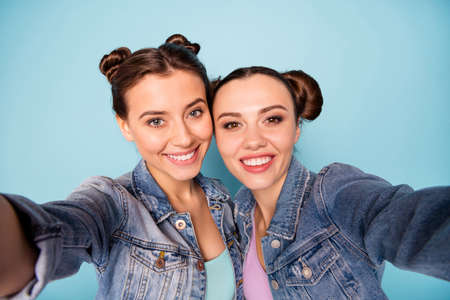 Friends forever. Close up photo of nice cute attractive teenagers  making photos memories spending weekends holidays dressed in blue denim clothing isolated on blue azure background