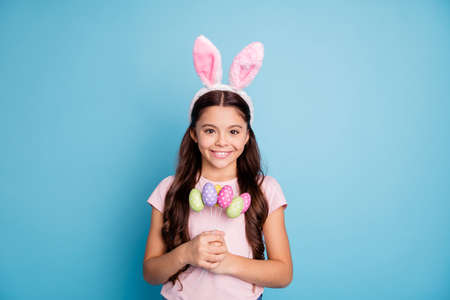 Spring season concept. Closeup photo portrait of positive glad nice pretty beautiful fashionable small lady demonstrating collection of colorful bright easter eggs in palms isolated pastel background
