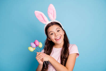 Closeup portrait of nice positive cheerful enjoying fest season girl holding a lot of painted in different colors easter eggs looking at camera isolated pastel background