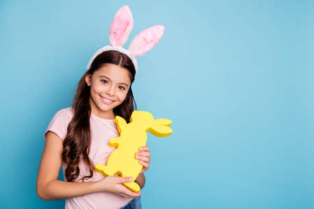 Closeup photo portrait of lovely cheerful pretty with beaming toothy smile charming in casual t-shirt girl holding hugging golden colored rabbit in hands isolated pastel background 写真素材