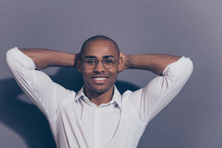 Close up photo amazing stunning dark skin he him his macho arms hands behind head perfect good mood toothy smile satisfied look refreshed shaved face wear specs white shirt isolated grey background