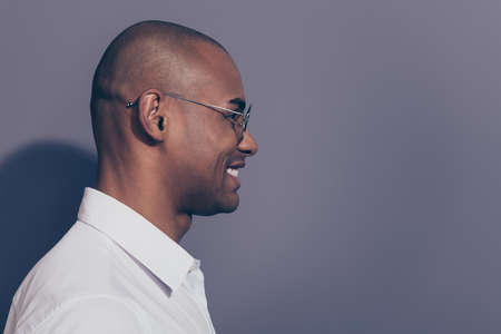 Close up side profile photo amazing dark skin he him his macho friendly attentively look empty space listen news novelty corporate meeting shaved face wear specs white shirt isolated grey background