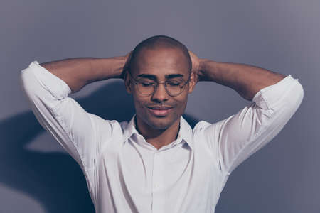 Close up photo amazing stunning dark skin he him his macho eyes closed arms hands behind head perfect good mood satisfied refreshed shaved face wear specs white shirt isolated grey background