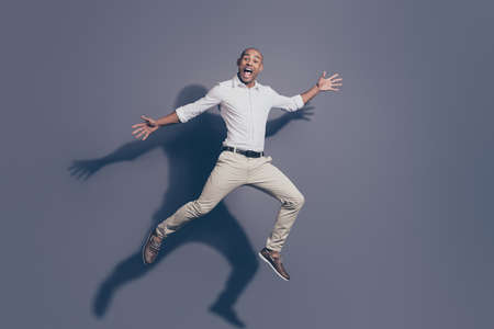 Full length body size photo amazing dark skin he him his macho shake hands arms up air jump high great mood playful crazy fooling around wear white shirt pastel pants isolated grey background