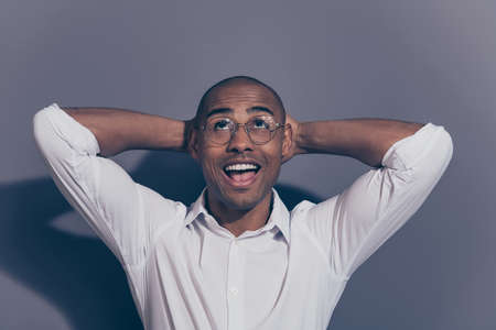 Close up photo amazing stunning dark skin he him his macho arms hands behind head perfect good mood satisfied look up empty space refreshed shaved face wear specs white shirt isolated grey background