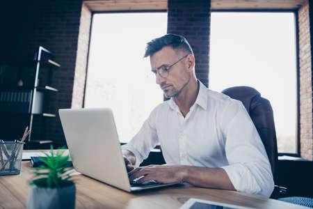 Cerrar perfil lateral arriba foto guapo él él su chico macho reflexionar pensativo tener inversores en línea moneda de chat de negocios carta atento cuaderno mesa sentarse silla de oficina usar especificaciones ropa formal camisa blanca