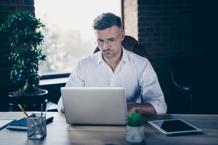 Close up photo handsome he him his macho guy best boss having online currency business chat email letters attentive notebook table sit big office chair wear specs formal-wear white shirt
