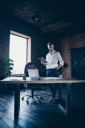 Vertical full length body size photo handsome he him his macho guy attentive look stats hold e-book e-reader watch webinar check numbers notebook table stand office wear specs formal wear white shirt Stock fotó