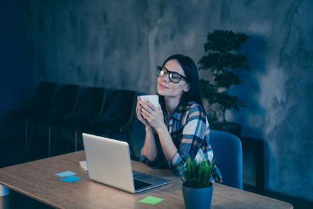 Portrait of her she nice cute lovely attractive cheerful brunette lady in checked shirt sitting in front of laptop enjoying having rest time at industrial loft style interior work place station