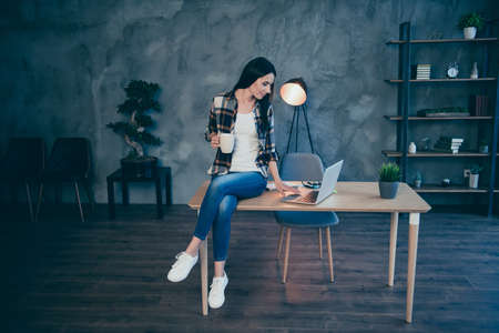 Full length body size view portrait of nice attractive charming cheerful brunette lady in checked shirt browsing news video chat sitting on desk at industrial loft style interior work place station