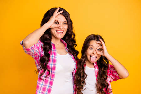 Portrait of nice attractive cheerful positive crazy foolish wavy-haired girls wearing checked shirt showing ok-sign like glasses isolated over bright vivid shine yellow background Stock Photo