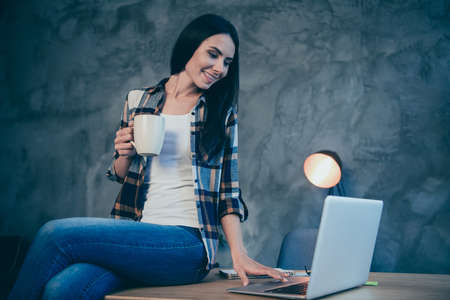 Portrait of nice cute attractive charming cheerful brunette lady wearing checked shirt free time browsing news video chat sitting on desk at industrial loft style interior work place station