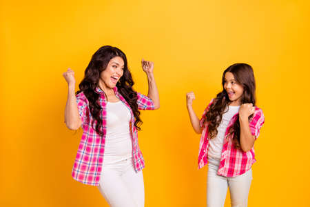 Portrait of nice-looking attractive groomed lovely cheerful positive wavy-haired girls wearing checked shirt accomplishment isolated over bright vivid shine yellow background Stock Photo