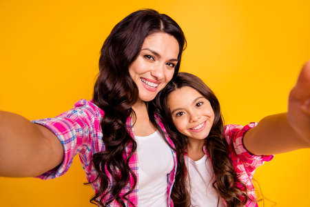 Close up photo two people brown haired mum mom small little daughter make take selfies for daddy wait him his he home house missing wear casual pink checkered plaid shirts isolated yellow background