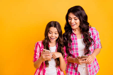 Close up photo beautiful mom small little daughter finger look what I have telephone smart phone yeah yes sms good news information wear casual pink plaid checkered shirts isolated yellow background 스톡 콘텐츠