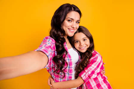 Close up photo two people funny brown haired mum mom small little daughter make take selfies daddy wait him his he home house miss wear casual pink checkered plaid shirts isolated yellow background