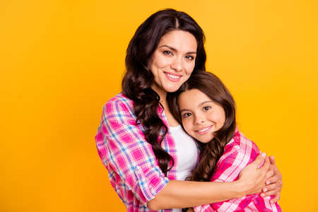 Close up photo two people funny brown haired she her ladies mum small little daughter hold each other hands arms close lovely wear casual pink checkered plaid shirts isolated yellow background