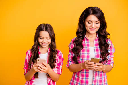 Close up photo beautiful brown haired mom small little daughter addicted telephones reader write sms got good news information wear casual pink plaid checkered shirts isolated yellow background Banco de Imagens