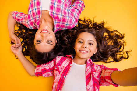 Close up top above high angle view photo beautiful she her models mom daughter caress weekend make take funky selfies lying floor wear casual pink plaid checkered shirts isolated yellow background