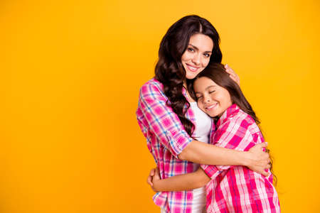 Close up photo two people funny brown haired she her ladies mum mommy treats small little daughter hold each other hands arms close wear casual pink checkered plaid shirts isolated yellow background