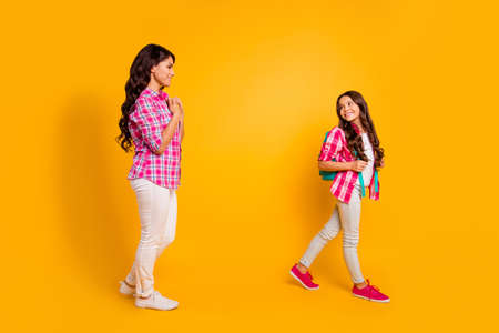 Close up side profile photo beautiful she her models ladies mom little daughter farewell study time see you soon watch motion away wear casual pink checkered plaid shirts isolated yellow background