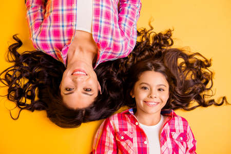 Close up top above high angle view photo beautiful she her models mom daughter adorable amazing long hair weekend lying floor wear casual pink plaid checkered shirts isolated yellow background