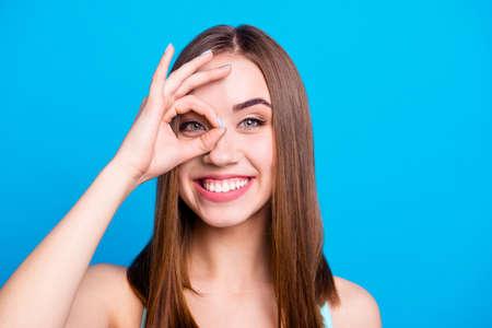 Nahaufnahme eines hübschen, sorglosen, verspielten Studenten, der die Finger in der Nähe des Auges platziert und die Entscheidung empfiehlt, Optionen einzeln auf buntem Hintergrund zu geben