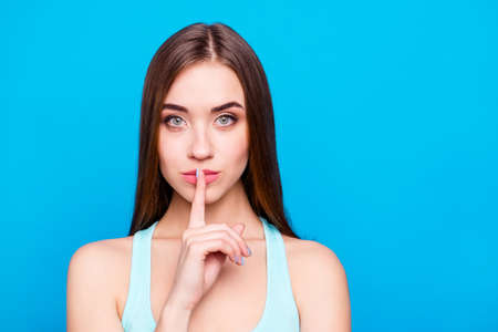 Close up portrait of attractive magnificent woman prevent share secrecy private information placing finger near lips saying hush feeling cool in modern outfit isolated on blue background Stock Photo