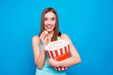 Close up photo beautiful amazing she her lady hold hands arms big large pop corn paper box container tasty appetizer movie night wear casual tank top outfit clothes isolated blue bright background