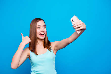 Close up photo beautiful amazing she her lady toothy hold hands arms telephone make take selfies thumb up advice new product followers wear casual tank top clothes isolated blue background
