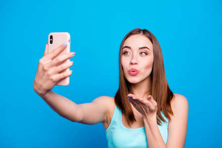 Close up photo beautiful amazing she her lady hold hands arms telephone make take selfies send air kisses followers wishing best day wear casual tank top clothes isolated blue background Reklamní fotografie