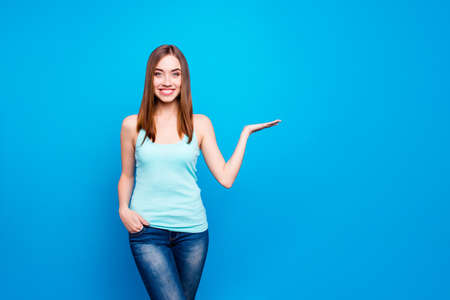 Portrait of charming pretty cool lady advise recommend adverts advertisements sale discounts give feedback new information isolated feel satisfied wearing jeans spring clothing blue background Stock Photo