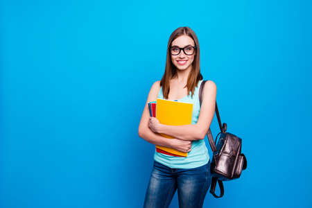 Close up photo beautiful amazing she her lady hold arms hands notebooks schoolgirl study applies pretty cute back bag wear specs casual jeans denim tank top clothes isolated blue background