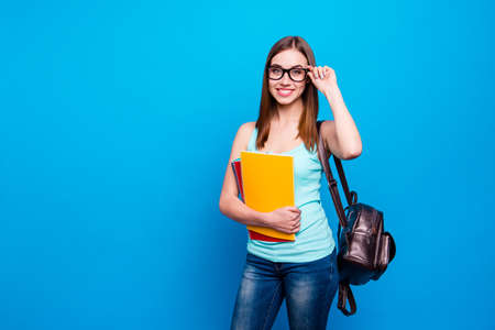 Close up photo funky beautiful amazing she her modern lady hold arms hands notebooks schoolgirl study applies pretty back bag wear specs casual jeans denim tank top clothes isolated blue background Stock Photo