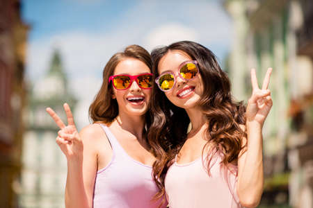Close up photo charming cute trendy pretty hairstyle best millennial travel trip long hair spring pastel clothing modern spec travel enjoy free time laugh make v-signs satisfied joy town center.