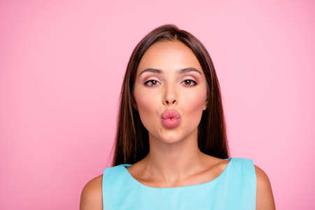 Close up photo of charming good-looking lady sending air kisses to guys boyfriends feeling affection wearing colorful outfit isolated on rose-colored background