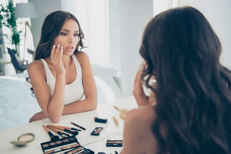 Portrait of nice-looking chic sweet tender attractive lovely stunning charming cute feminine well-groomed wavy-haired lady applying facial cream in light white interior room Stock Photo