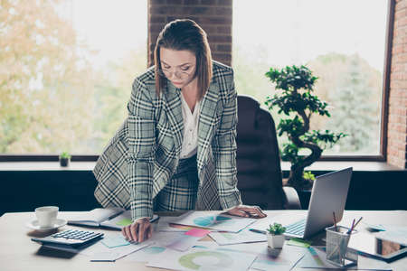Close up photo beautiful she her business busy lady ponder pensive contemplation look documents charts accountant analyzer stand lean table office wear specs formal-wear checkered plaid suit Foto de archivo