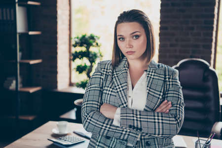 Close up photo beautiful amazing reliable she her business busy lady not smiling hands arms crossed glass cup hot beverage stand leaning table office wearing specs formal-wear checkered plaid suit Stock Photo