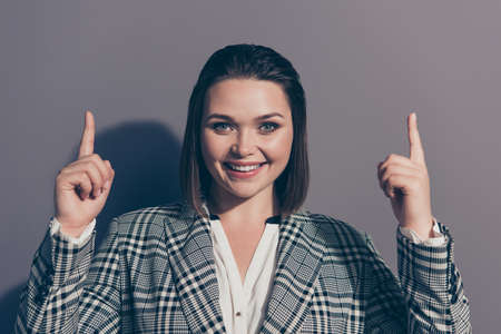 Close-up photo studio portrait of cheerful clever smart intelligent excited confident office lady wearing checkered jacket holding hands up looking at camera isolated gray background Stock Photo