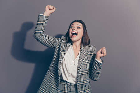 Close up photo portrait of cheerful funky funny glad winning prize with opened mouth lady holding raising fists up isolated grey background
