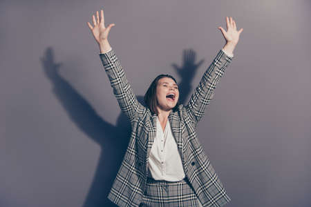 Closeup photo portrait of beautiful cheerful excited screaming with open mouth raising fists hands up isolated grey background