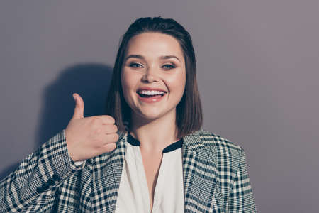 Closeup photo portrait of positive excited cheerful optimistic glad attractive she her office lady giving making finger up wearing plaid collar blazer isolated grey background