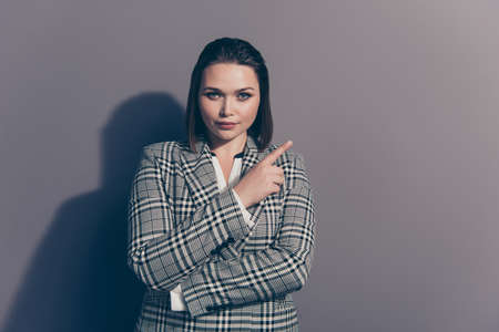 Closeup photo portrait of confident serious charming thoughtful office lady making choice pointing with forefinger looking at camera isolated grey background