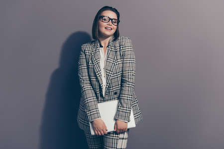 Adorable dreamy  dreamy cute charming elegant graceful pretty attractive she her woman using netbook for work wearing checkered plaid suit pants trousers isolated grey background Stock Photo