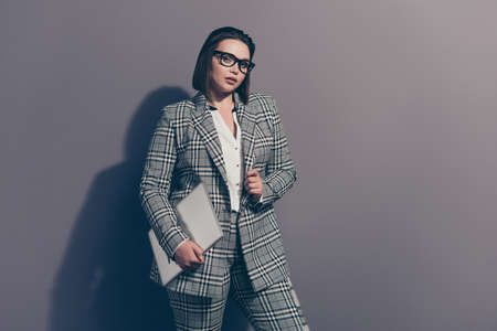 Photo portrait of lovely beautiful trendy style stylish trend graceful elegant strict she her woman in classic classy checkered plaid suit holding silver netbook isolated grey background Stock Photo