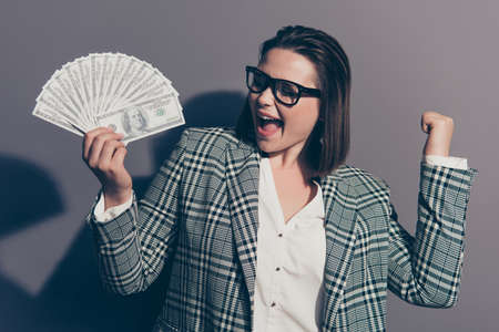 Closeup photo portrait of screaming yelling shouting excited cheerful she her lady demonstrating lot of money in arm isolated grey background