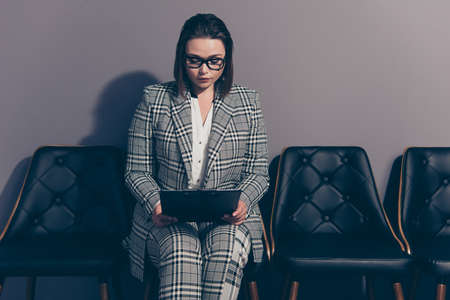 Serious thoughtful clever smart intelligent she her lady holding document in hands wearing checkered plaid suit pants isolated grey background